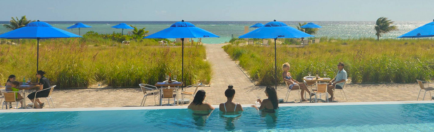 Guests In The Pool Overlooking The Ocean at East Bay Resort South Caicos