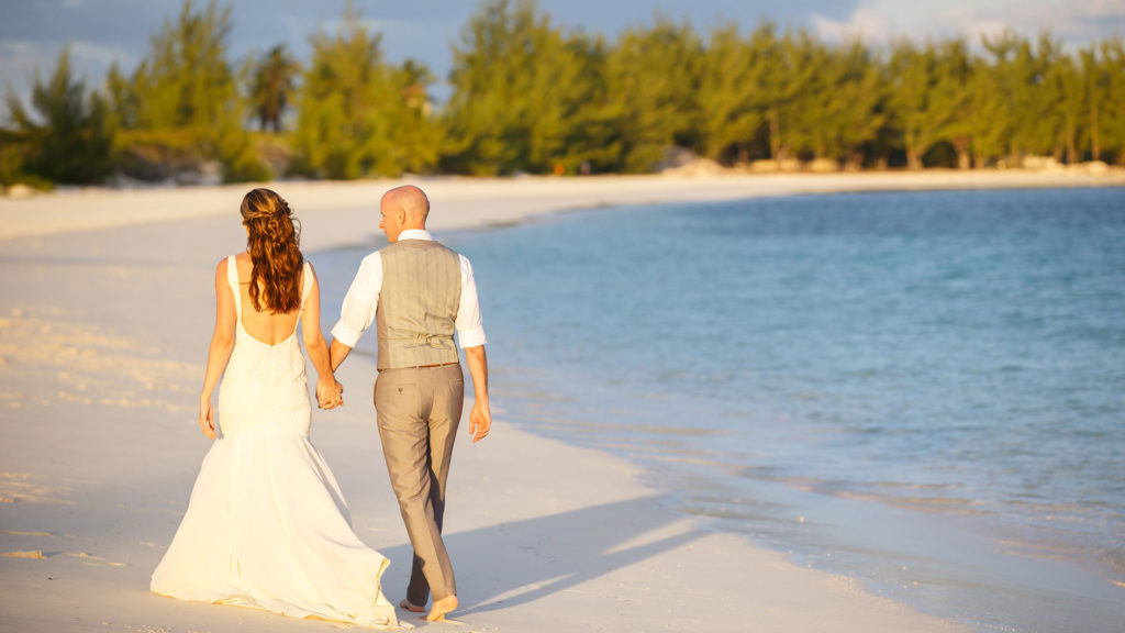 The Bride And Groom Walk Together On The Beach After Their Wedding Ceremony