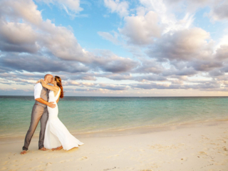 The Bride And Groom Kiss On The Beach After Ther Wedding Ceremony