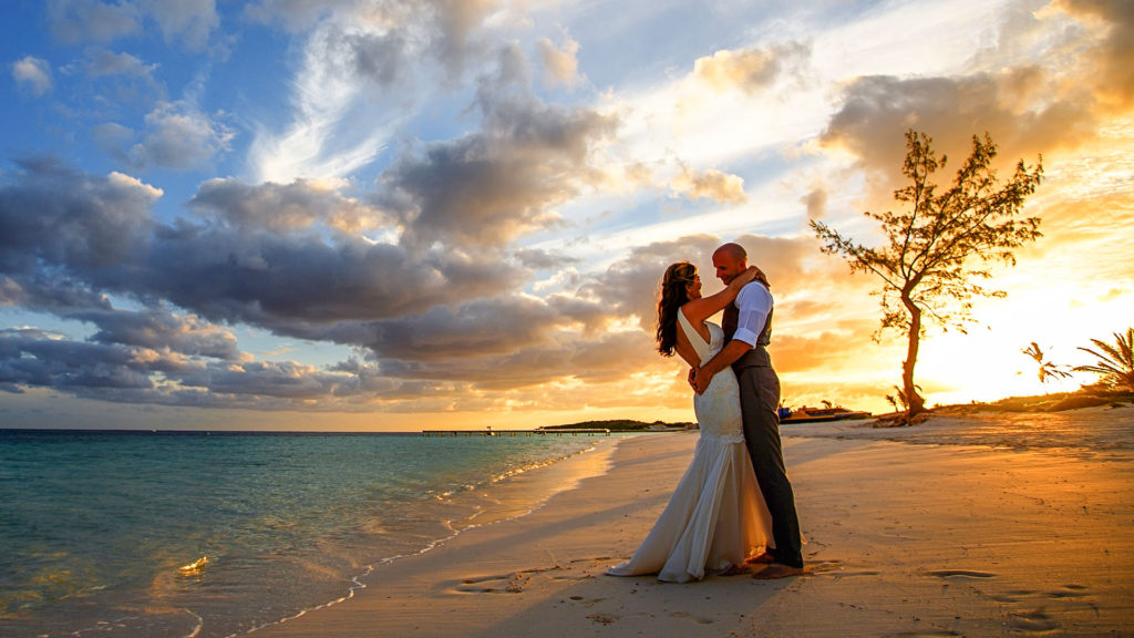 The Bride And Groom Pose On The Beach With The Sun Setting After Ther Wedding Ceremony